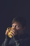 美丽的妇女饮用的咖啡或茶在暗室 免版税库存图片