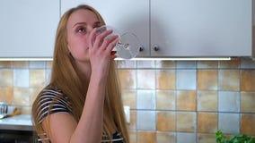 美丽的妇女饮用的科涅克白兰地在家 股票录像