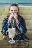 年轻美丽的妇女饮用的茶热奶咖啡画象在时髦咖啡馆商店 库存图片
