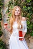 美丽的妇女饮用的酒户外 年轻白肤金发的秀丽画象在获得的葡萄园里乐趣,享用玻璃  免版税库存照片
