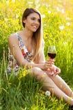 年轻美丽的妇女饮用的酒户外 免版税库存照片