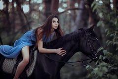 美丽的妇女骑乘马在森林里 免版税库存图片