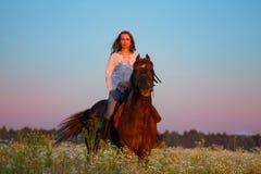 美丽的妇女骑乘马画象在日落的 免版税库存照片