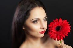 美丽的妇女,在她的面孔的轻的构成在一朵美丽的红色花的手上 女性纵向 开花妇女 妇女和f 免版税库存图片