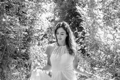 美丽的妇女,新娘走通过叶茂盛森林的,森林地在一明亮的晴朗的夏天` s天 免版税库存照片