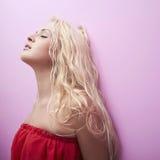 美丽的妇女年轻人 红色礼服 性感的金发碧眼的女人 白肤金发的女孩 卷曲发型 桃红色墙壁 免版税库存照片