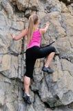 美丽的妇女登山家在山上升 免版税库存照片