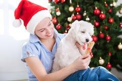 年轻美丽的妇女给当前骨头她的christma的狗 免版税库存图片
