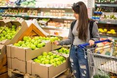 美丽的妇女购物的蔬菜和水果在超级市场 库存照片