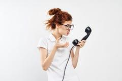 年轻美丽的妇女玻璃的和在轻的背景的一件背心的拿着一个输送路线电话,情感,愤怒 免版税库存照片