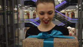 美丽的妇女画象一件黑礼服的采取礼物 他看照相机和微笑 在商店里面 室内 股票录像