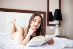 年轻美丽的妇女画象在床上的,早晨读了书并且吃蛋糕 免版税库存照片
