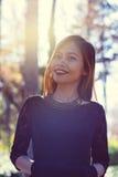 年轻美丽的妇女画象在有好的早晨阳光的公园 库存图片
