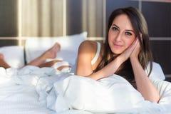 美丽的妇女画象在看在照相机的床上的 免版税库存照片