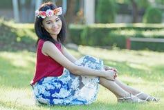 年轻美丽的妇女画象坐草,在绿色bac 库存图片