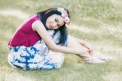 年轻美丽的妇女画象坐草 免版税库存图片
