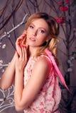 年轻美丽的妇女画象天使服装的有桃红色胜利的 免版税图库摄影