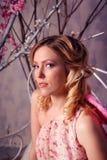 年轻美丽的妇女画象天使服装的有桃红色胜利的 免版税库存照片