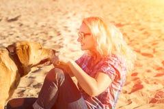年轻美丽的妇女画象太阳镜的坐拥抱金毛猎犬狗的沙子海滩 有狗的女孩由海 免版税库存照片