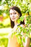 年轻美丽的妇女画象春天开花树的 图库摄影