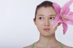 年轻美丽的妇女画象有在她的耳朵后被卷起的一朵大桃红色花的,演播室射击 图库摄影