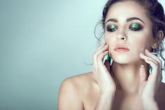 年轻美丽的妇女画象有完善的接触她的与被修剪的手指的皮肤和明亮的构成的面孔 库存照片