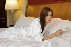 美丽的妇女画象有杯子的在床上 库存图片