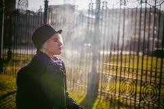 年轻美丽的妇女画象有白发的,在一件黑外套、裙子和黑帽会议,抽一根电子香烟 免版税图库摄影