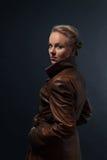 年轻美丽的妇女画象棕色皮革外套的 库存照片
