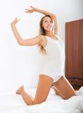 美丽的妇女画象白色板料的在床上 库存照片