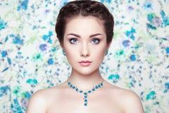 年轻美丽的妇女画象花背景的  免版税图库摄影