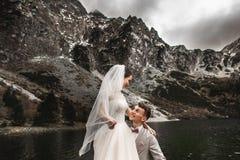 美丽的婚姻的photosession 新郎盘旋他的年轻新娘,湖Morskie Oko的岸的 ?? 免版税库存图片