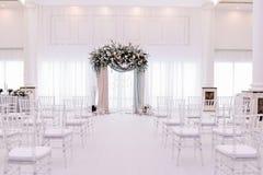 美丽的婚礼拱道 用极好和银色布料和花装饰的曲拱 免版税库存图片