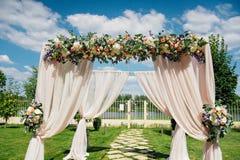 美丽的婚礼曲拱,装饰用biege布料和花 免版税库存图片