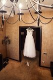美丽的婚礼礼服垂悬在屋子里的,新娘辅助部件, 库存图片