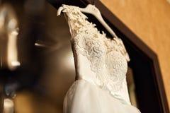 美丽的婚礼礼服垂悬在屋子里的,新娘辅助部件, 免版税库存照片