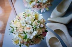 美丽的婚礼花束和白色鞋子 库存图片