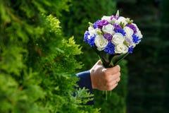 美丽的婚礼花束在人的手上 免版税库存图片