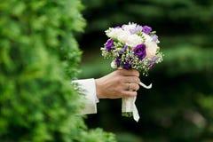 美丽的婚礼花束在人的手上 免版税图库摄影