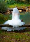 美丽的婚礼花束在新娘的手上和教会在背景中 免版税库存照片