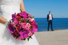 美丽的婚礼花束在新娘的手上背景的  库存图片