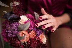美丽的婚礼花束在新娘的手上 时髦和现代婚礼在marsala颜色开花 新娘的手与 免版税图库摄影
