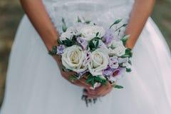 美丽的婚礼花束在新娘的手上 牡丹上升了,棉花,玫瑰 白色和Vioolet 时髦和现代婚礼花 图库摄影