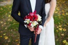 美丽的婚礼花束在新娘的手上 免版税库存照片