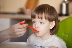 美丽的婴孩吃从妈妈` s手的粥 母亲喂养有匙子的儿子 有长的金发和大蓝眼睛的p男孩 库存图片