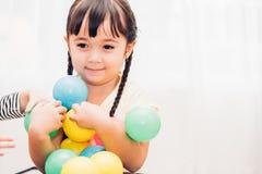 美丽的婴孩哄骗打五颜六色的球的女孩幼儿园 免版税图库摄影