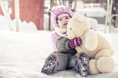 美丽的婴孩拥抱玩具长毛绒熊坐雪在公园在冷的晴朗的冬日在寒假期间 库存图片