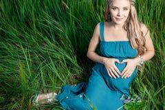 美丽的嫩孕妇坐绿草 免版税图库摄影