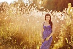 美丽的嫩孕妇微笑并且享受一个晴朗的夏天 免版税库存照片