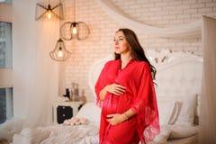 美丽的孕妇在典雅的红色便服穿戴了 库存照片